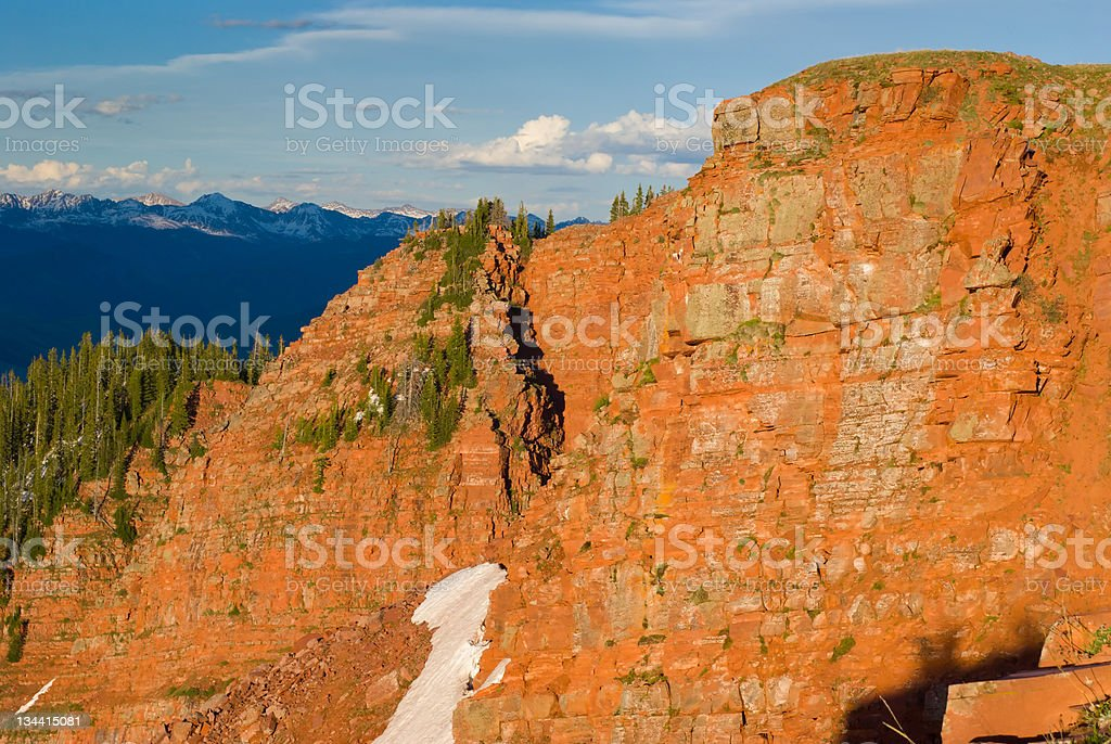 Alpenglow on Red Rock Cliffs and Rocky Mountains Colorado royalty-free stock photo