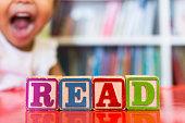"Closeup of kids alphabet wooden blocks arranged to spell ""read"""