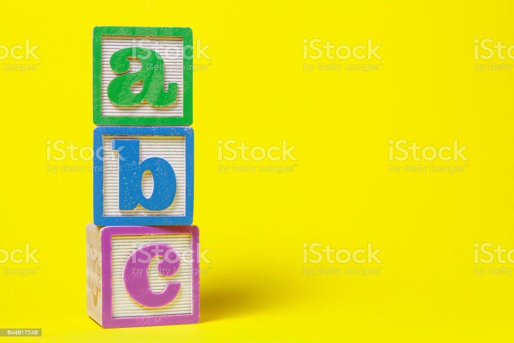 ABC Alphabet blocks stacked up on yellow background stock photo