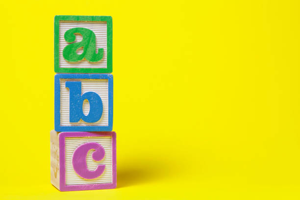 abc alphabet blocks stacked up on yellow background - alphabetical order stock pictures, royalty-free photos & images