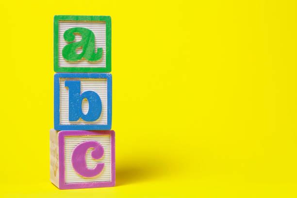 ABC Alphabet blocs empilés vers le haut sur fond jaune - Photo
