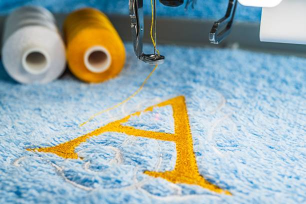 a alphabet design on towel in hoop of embroidery machine - embroidery machine stock pictures, royalty-free photos & images