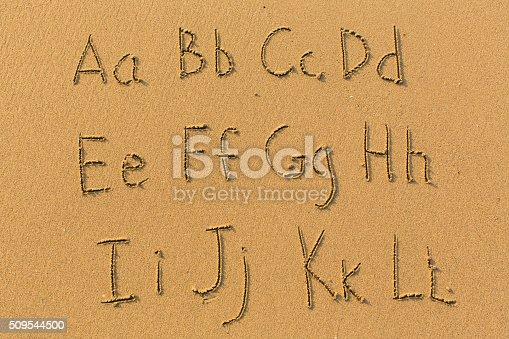 istock Alphabet drawn on the sand of a beach. 509544500