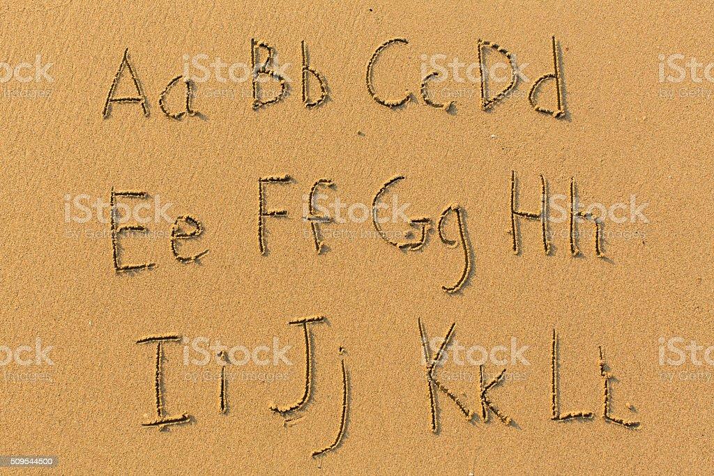 Alphabet drawn on the sand of a beach. stock photo