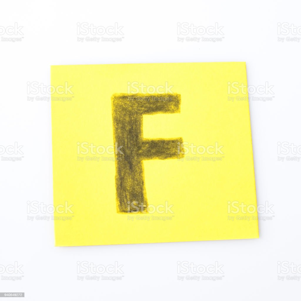 F alphabet letter handwrite on a yellow paper composition stock photo