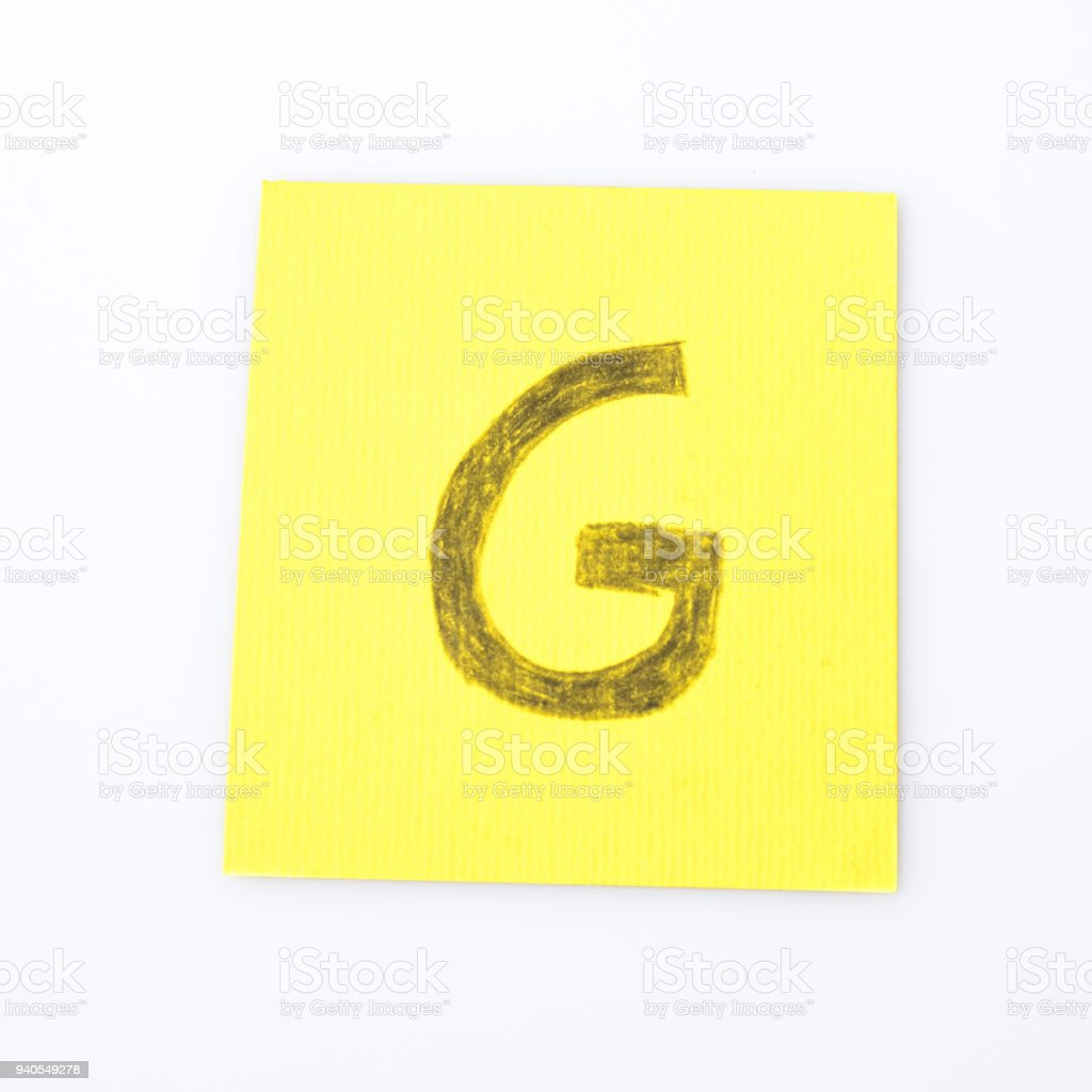 G alphabet letter handwrite on a yellow paper composition stock photo