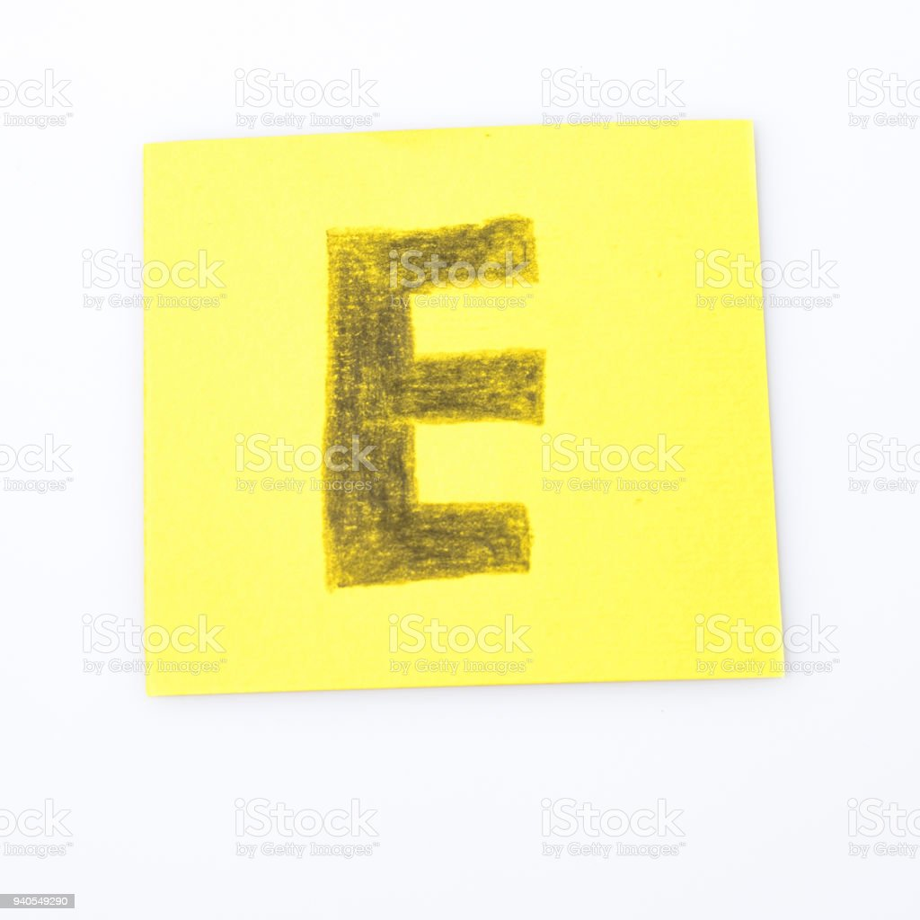 E alphabet letter handwrite on a yellow paper composition stock photo