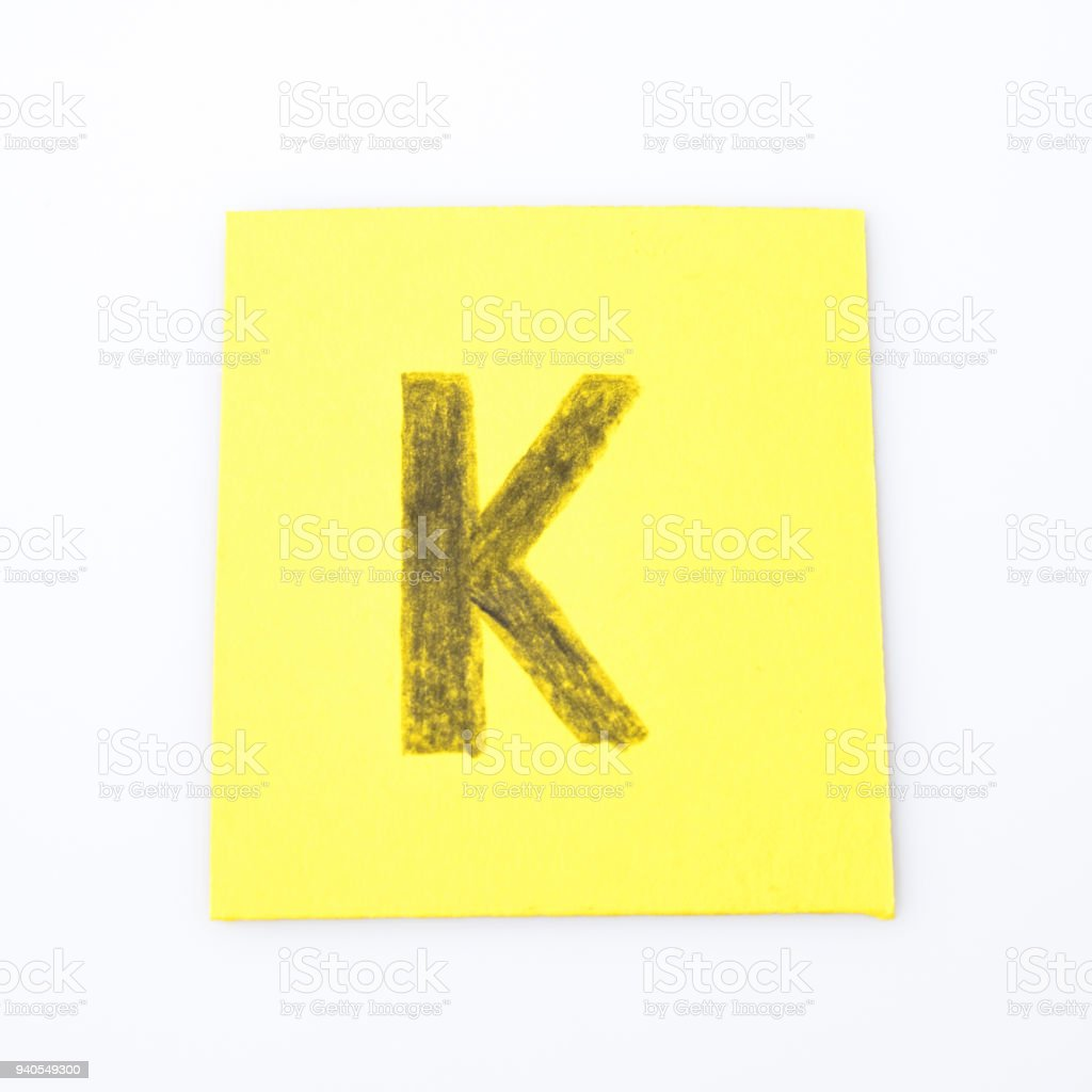 K alphabet letter handwrite on a yellow paper composition stock photo