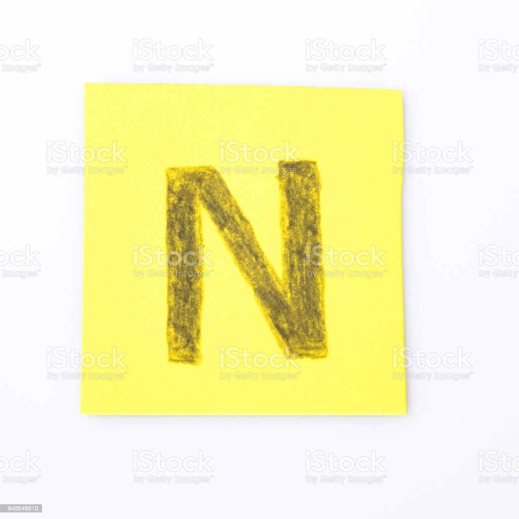 N alphabet letter handwrite on a yellow paper composition stock photo