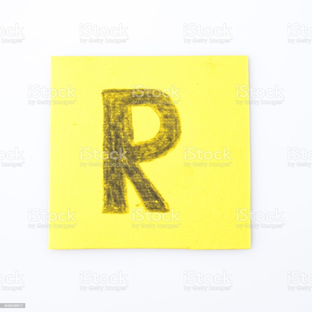 R alphabet letter handwrite on a yellow paper composition stock photo