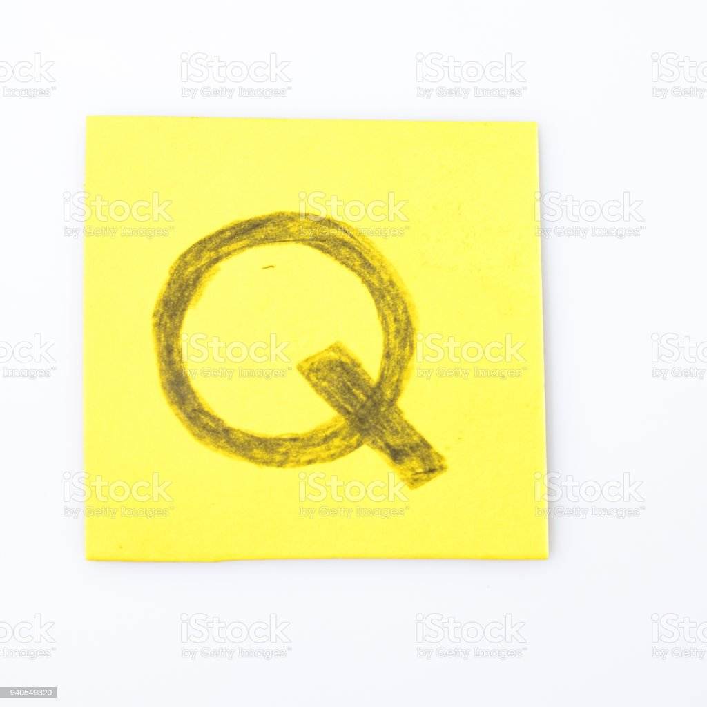Q alphabet letter handwrite on a yellow paper composition stock photo