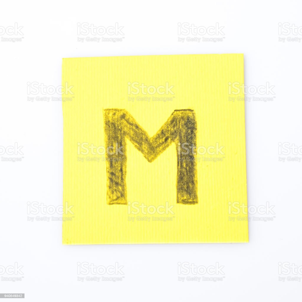 M alphabet letter handwrite on a yellow paper composition stock photo