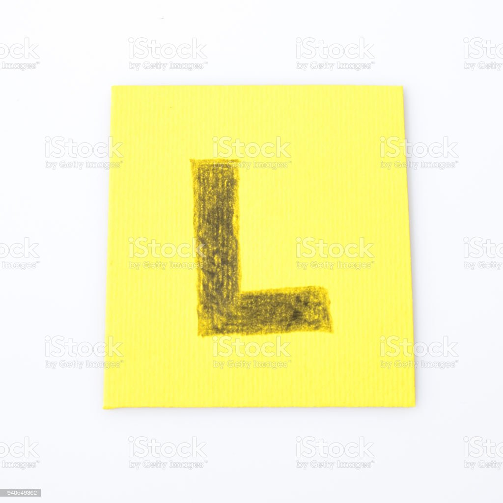 L alphabet letter handwrite on a yellow paper composition stock photo