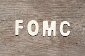 Alphabet letter in word fomc (abbreviation of federal open market committee) on wood background