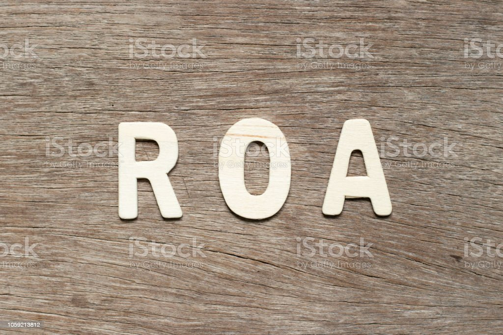 Alphabet letter in word ROA (Abbbreviation of Return on assets) on wood background stock photo