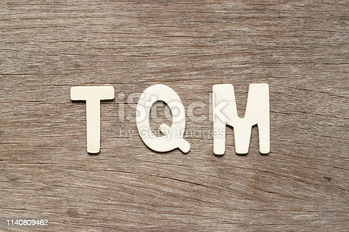 Alphabet letter in word TQM (Abbreviation of total quality management) on wood background