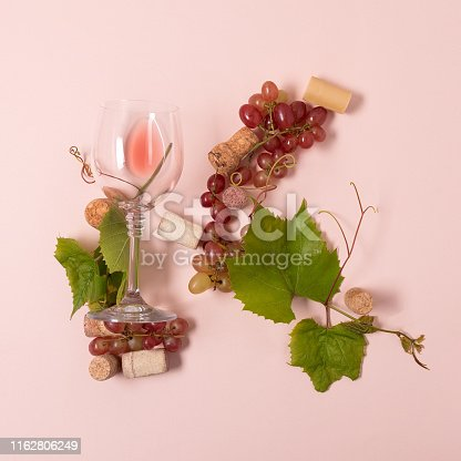 istock Alphabet. Letter K made of wineglasses with rose and white wine, grapes, leaves and corks lying on pink background. Wine degustation concept. Flat lay. Top view 1162806249