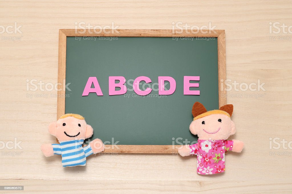 Alphabet letters ABCDE and children dolls on blackboard. royalty-free stock photo