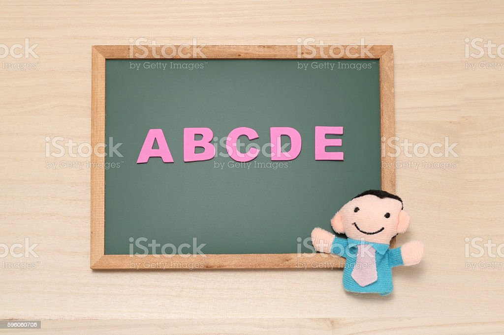 Alphabet letters ABCDE and man doll on blackboard. royalty-free stock photo