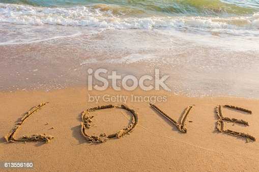 istock alphabet letters love handwritten in sand on beach 613556160
