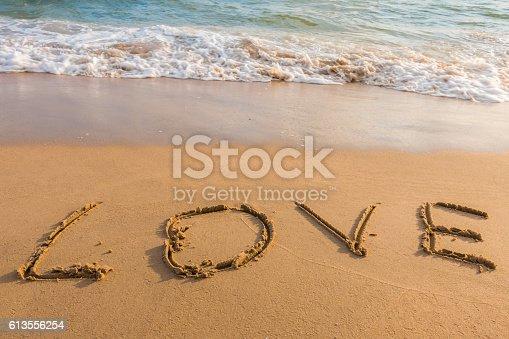 istock alphabet letters love handwritten in sand on beach 613556254