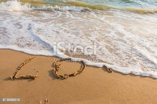 istock alphabet letters love handwritten in sand on beach 613556310