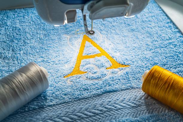 alphabet logo on towel in hoop of embroidery machine - embroidery machine stock pictures, royalty-free photos & images