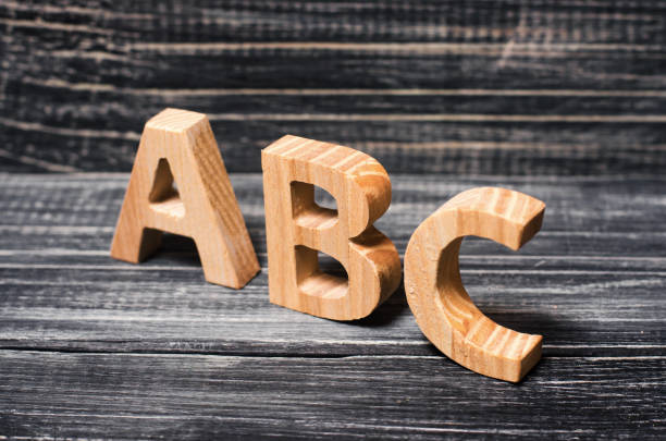 Alphabet made of wood on the background of a board, ebony. Concept of education, English. English letters, retro. stock photo