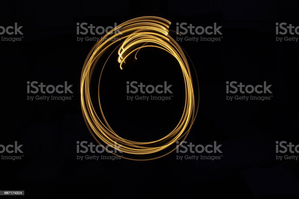 Alphabet Series - Letter O - Gold Light Painting Photography against a black background stock photo