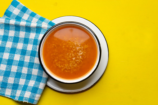 Alphabet soup pasta on yellow background