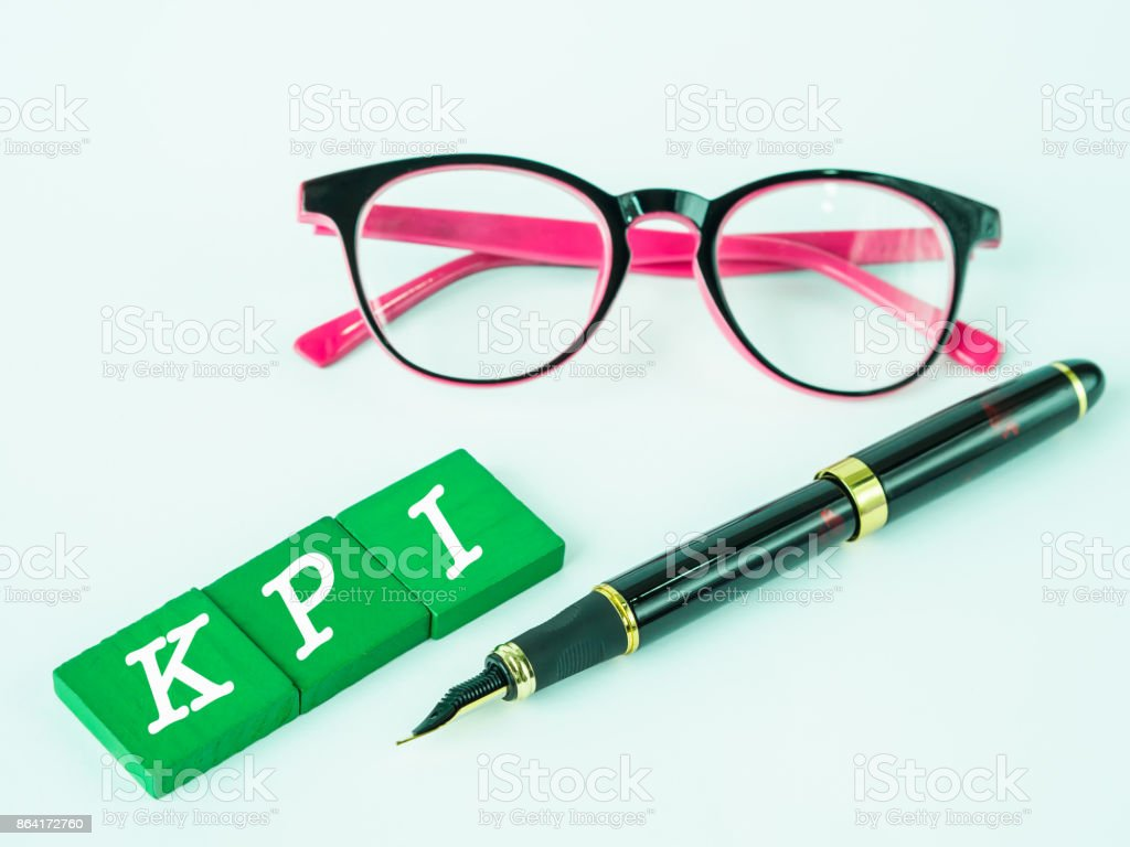 KPI alphabet with black pen and pink glasses on white table background. royalty-free stock photo