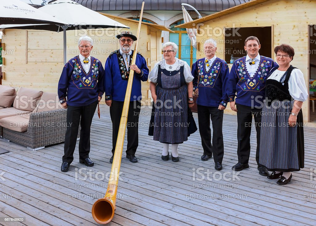 Alphorn player and senior people in traditional Swiss costumes stock photo
