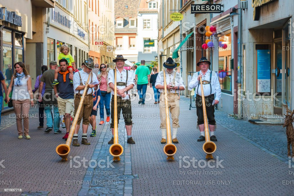 Alphorn player in traditional Bavarian costumes performing on the street of Heidelberg at the fall folk festival. Heidelberg, Germany - September 24 2016. stock photo