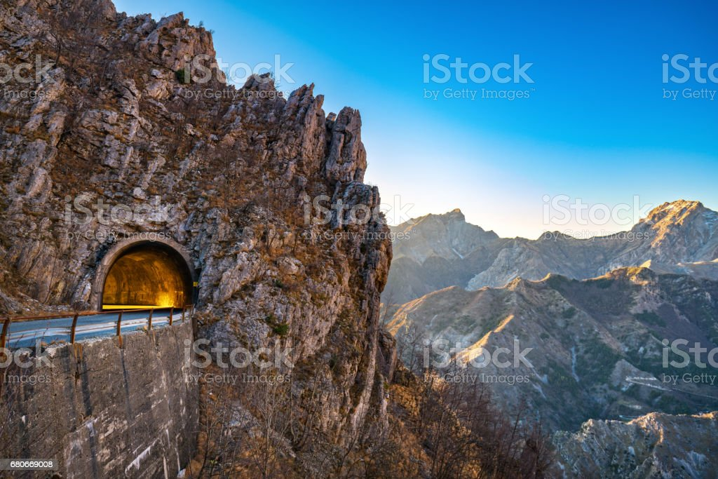 Alpi Apuane mountain road pass and tunnel view at sunset. Carrara, Tuscany, Italy. stock photo
