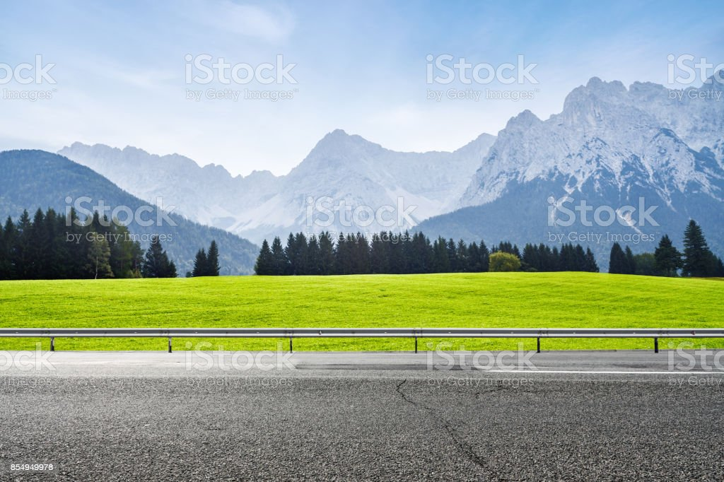 Alpine green meadow and asphalt road stock photo