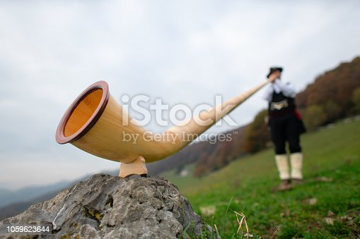 Alpine horn. A man plays in an alpine valley.