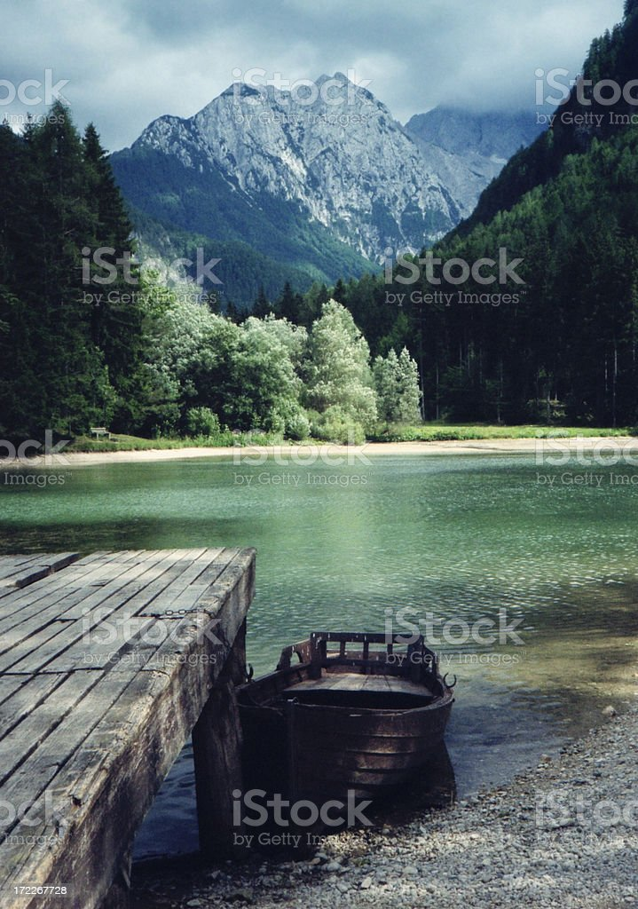 Alpine Lake in Mountains with Small Boat and Dock stock photo