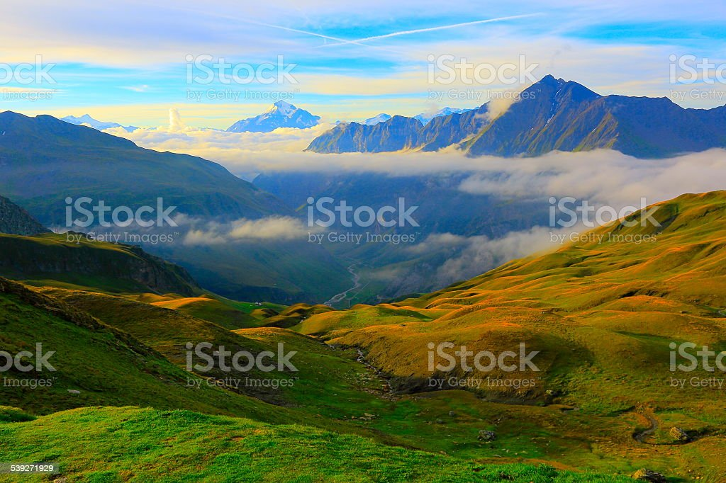 Alpine landscape above clouds and valley at sunrise stock photo