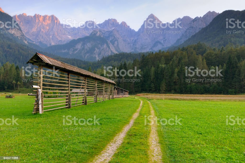 Alpine landscape with dirt road crossing fresh green meadow and traditional hayrack. Dramatic rocky mountain peaks on background stock photo