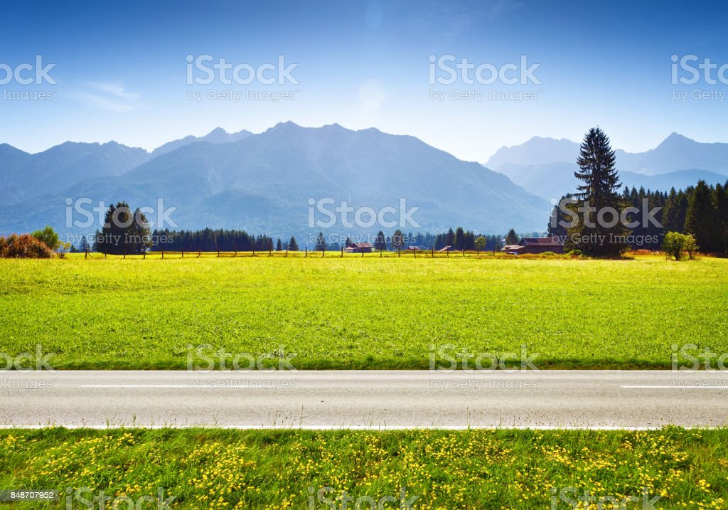 Alpine meadow and road, mountains on background stock photo