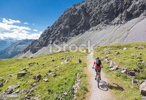 A female mountainbiker is riding on a scenic, narrow single trail high above Davos, Switzerland. Davos is a large alpine city in the canton of Graubünden. The region is famous for lots of outdoor sports activities in summer as well as in wintertime. Canon EOS 5D Mark IV, 1/400, f/5, 24 mm.
