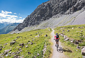 A female mountainbiker is riding on a scenic, narrow single trail high above Davos, Switzerland. Davos is a large alpine city in the canton of Graubünden. The region is famous for lots of outdoor sports activities in summer as well as in wintertime.\nCanon EOS 5D Mark IV, 1/400, f/5, 24 mm.