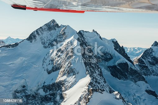 900763322 istock photo Alpine scenery from the air through the airplane window 1088429116