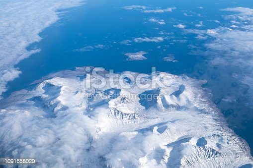 621114928istockphoto Alpine scenery from the air through the airplane window 1091558020
