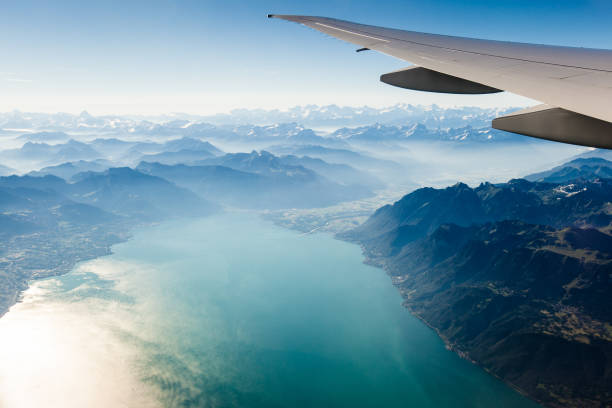 alpine scenery from the air through the airplane window - travel imagens e fotografias de stock