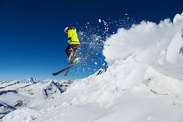 Alpine skier on piste, skiing downhill Alpine skier skiing downhill, blue sky on background ski stock pictures, royalty-free photos & images