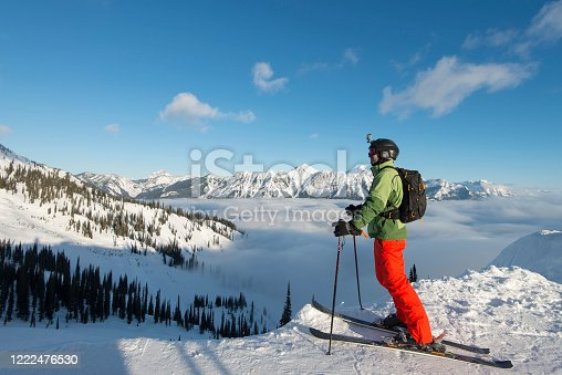 603993820 istock photo Alpine skier relaxes above fog bank, mountains and valley 1222476530
