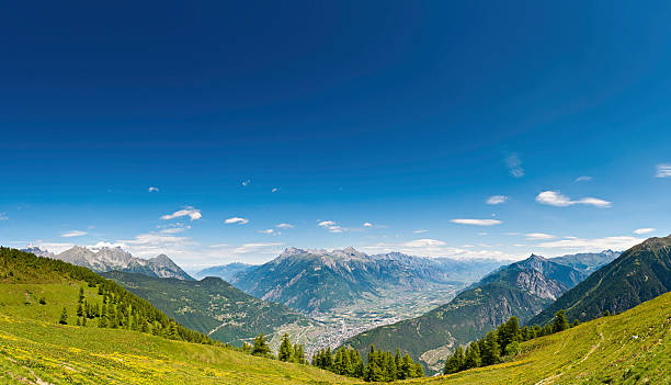 Alpine summer mountain meadow panorama Switzerland Vibrant green Alpine meadow high above the resort town of Martigny, Switzerland, under panoramic summer skies. ProPhoto RGB profile for maximum color fidelity and gamut. swiss alps stock pictures, royalty-free photos & images