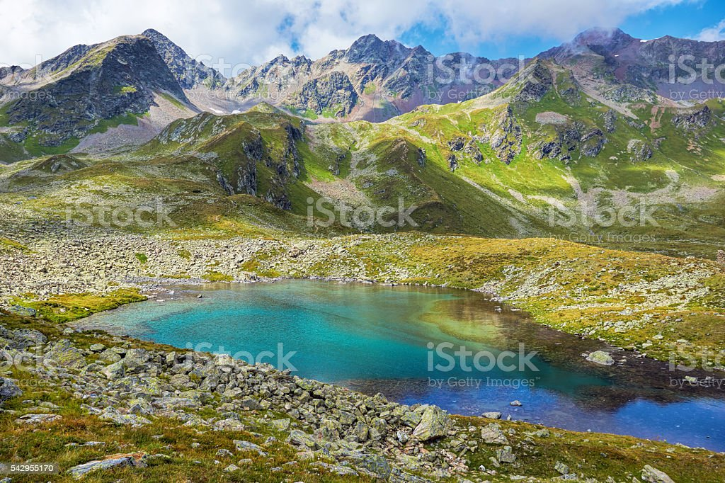 Alpine Valley with lake and mountain peaks stock photo