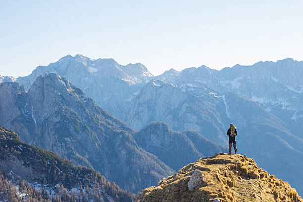 alpinist enjoying the view over the mountains in the alps - mountain range stock photos and pictures